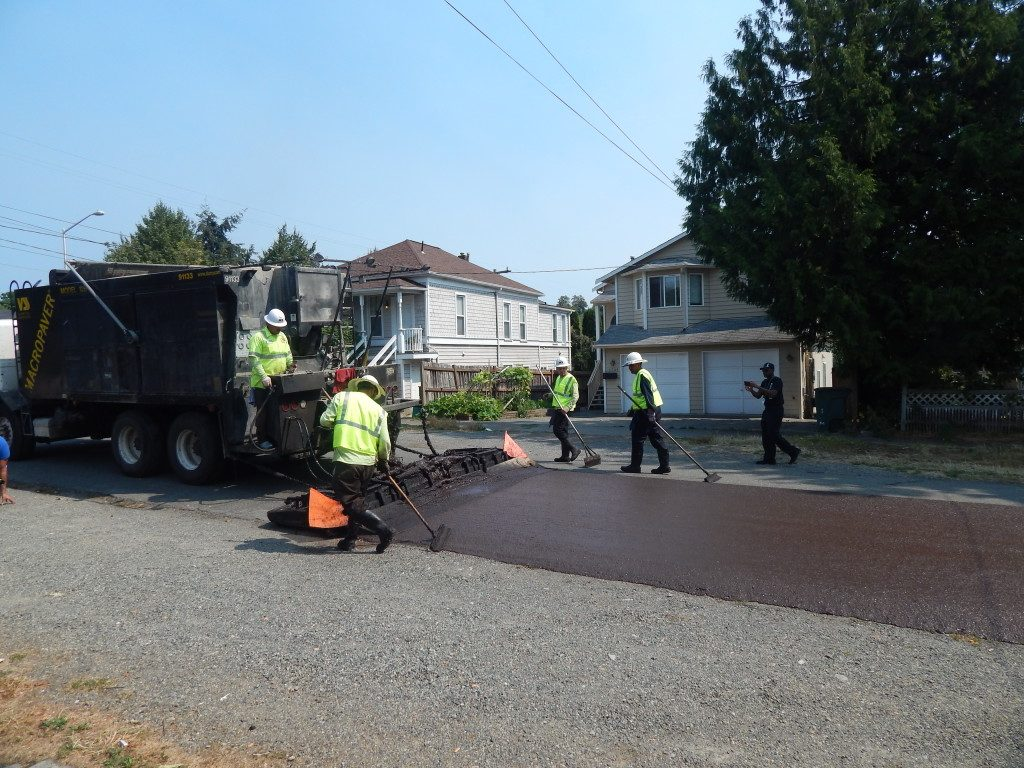 Microsurfacing crew at work, spreading emulsion